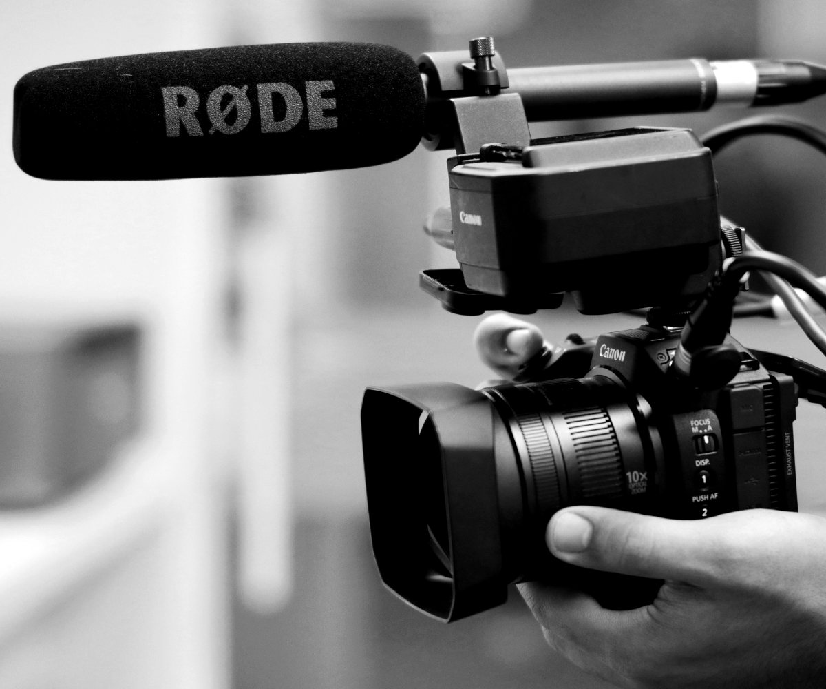 Person holding video camera - writing for b2b video scripts - Etymon